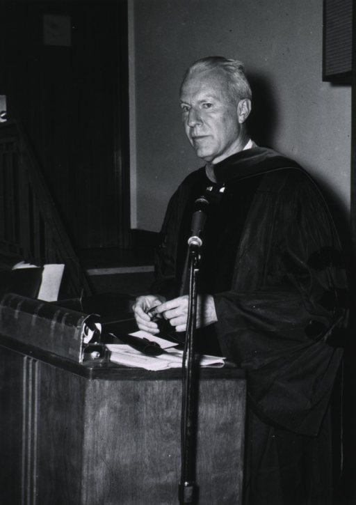 <p>Three-quarter length, face to left, standing behind a podium, wearing academic robes.</p>