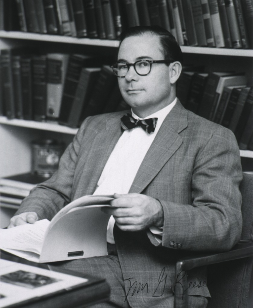 <p>Half length, full face, seated, holding notebook with books in background.</p>