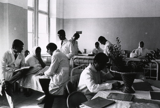 <p>Interior view of the woman's ward at the Pahlavi Hospital, Tehran: (left) three medical students discuss the case of a patient at her bedside; other students and patients are seen in the room.</p>