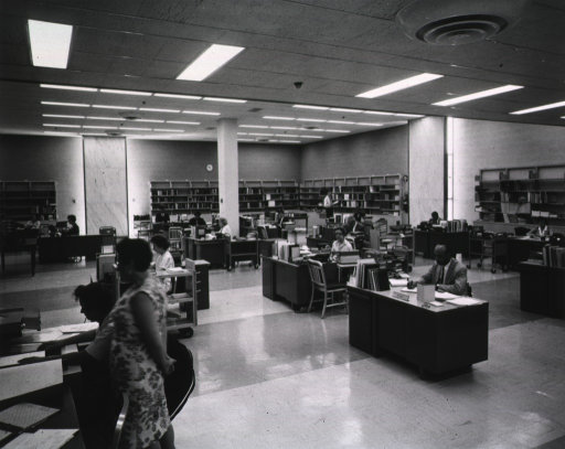 <p>Interior view: Among the reference staff at desks are Gerald Garner and Ms. Mosley.  Shelves line the walls.</p>