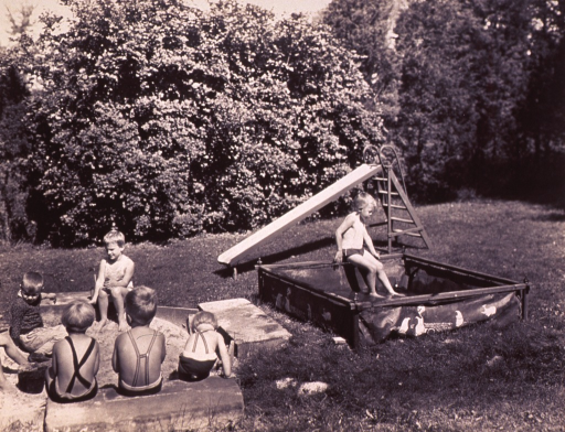 <p>In a backyard, children are playing in a sandbox; one child is playing in a canvas swimming pool; behind the pool is a slide.</p>