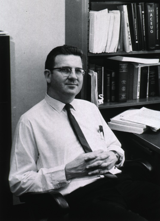 <p>Three-quarter length, right pose, seated in office; wearing glasses.</p>