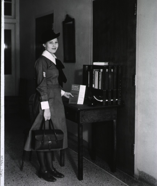<p>A nurse, in uniform, stands beside a table holding a book.</p>