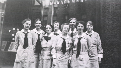 <p>Eight members of the staff stand outside a building.</p>