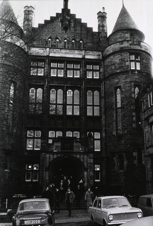 <p>Exterior view: a group of students are standing on the steps at the entrance to a large stone building (the Royal Infirmary at Edinburgh University).</p>