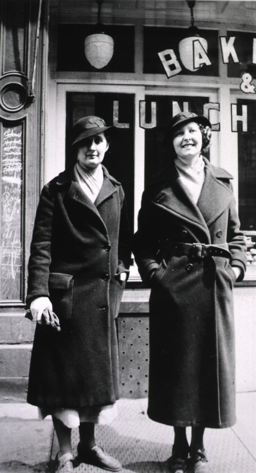 <p>Two female students stand outside of a bakery/deli.</p>