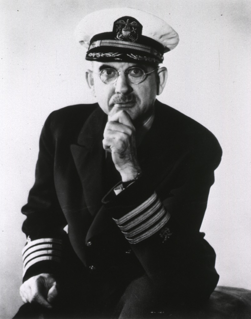 <p>Full front pose of unidentified seated man in military unifirm, wearing hat and glasses.</p>