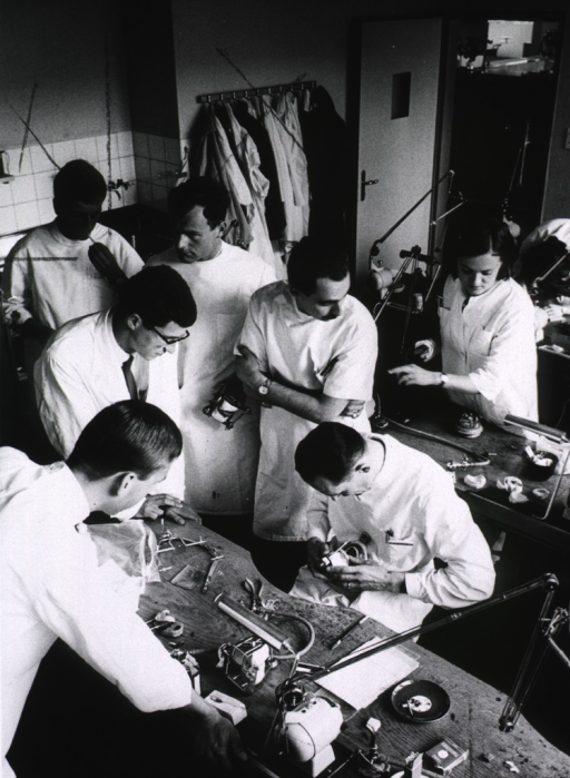 <p>Interior view: a group of dental students observe the manufacture of dentures. In the background one student prepares to light-up a cigarette.</p>