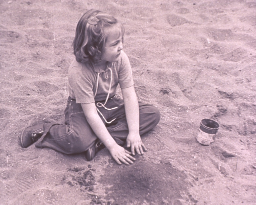 <p>A little girl is playing in the sand.</p>