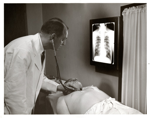 <p>Dr. Luther L. Terry examines a patient and an x-ray at the Baltimore Marine Hospital.</p>