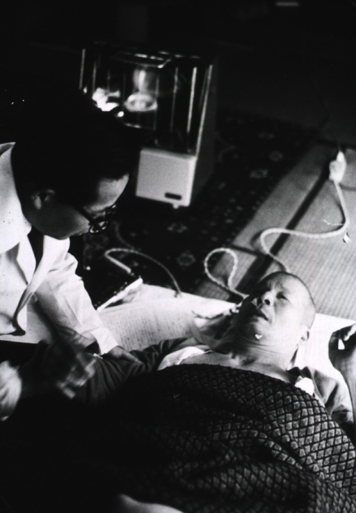 <p>A man is lying on a mat on the floor, the physician is kneeling next to him.</p>