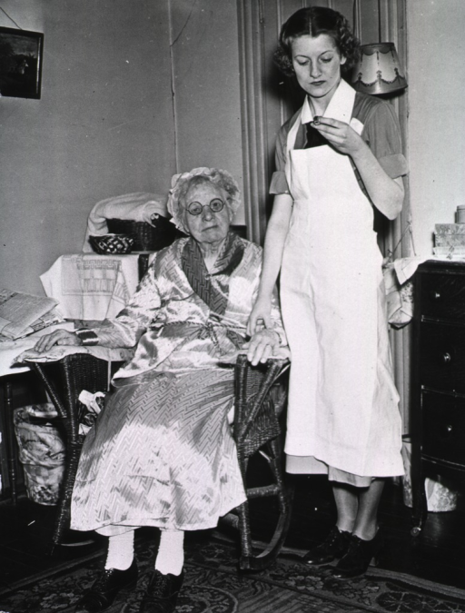<p>A nurse takes the pulse of an elderly woman who is sitting in a wicker rocking chair.</p>