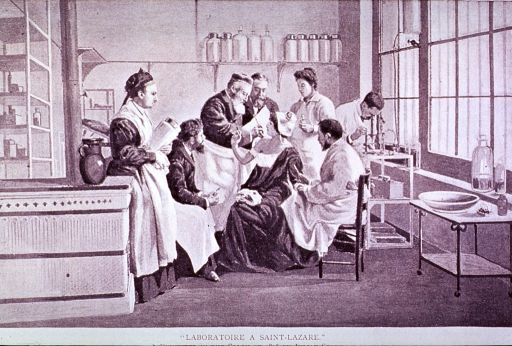 <p>Interior view: an elderly physician/scientist treats the shoulder of a young woman; the procedure is observed by several colleagues; in the background, a man is looking into a microscope.</p>