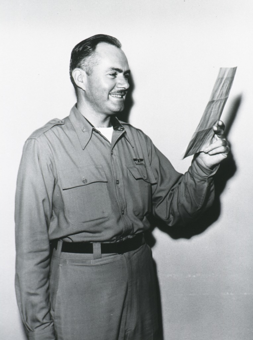 <p>Standing, right face, holding paper, uniform.</p>