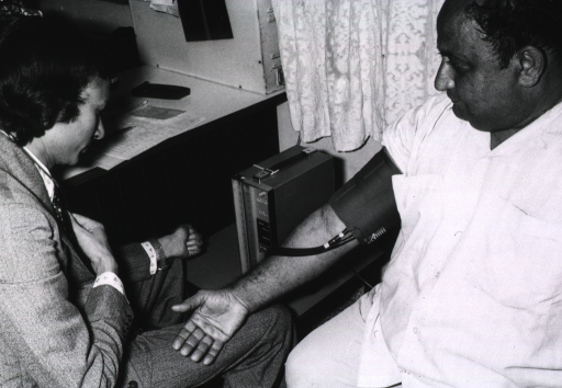 <p>A man is connected to a small portable device that measures blood pressure; a physician, sitting next to the man, is monitoring the machine.</p>
