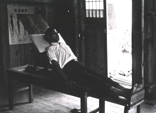 <p>Interior view:  a young man is reclining on a partially raised wooden apparatus; his legs are extended and his feet are resting against a board.</p>