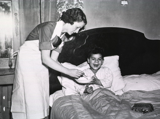 <p>A nurse feeds a young boy who is sick in bed.</p>