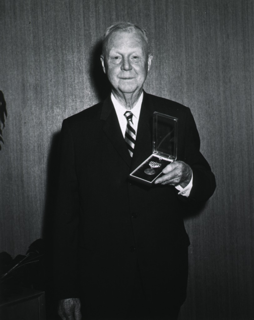 <p>Three-quarter length, standing, holding Outstanding Civilian Service Medal received at presentation ceremony, June 29, 1965.</p>