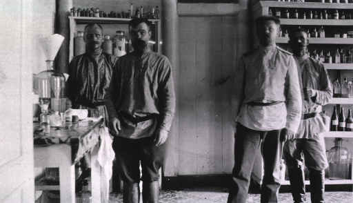 <p>Four staff personnel stand in the dispensary at Military Mobile Hospital No. 53.</p>