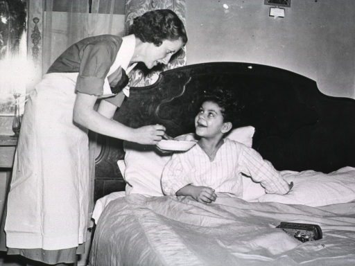 <p>A nurse feeds a sick young boy who is in bed.</p>