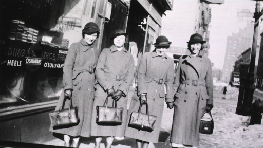 <p>Four nurses, in uniform, stand in front of a store.</p>