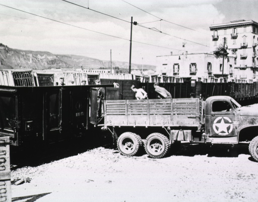 <p>Men unload construction materials from the bed of a truck.</p>