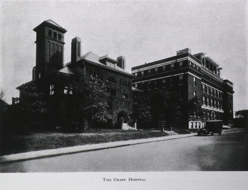 <p>Exterior view: the original hospital building is on the left; on the right is the annex which was added in 1912. A truck (ambulance?) is parked in the street at the entrance to the original building.</p>
