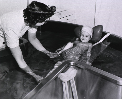 <p>Poliomyelitis patient is receving treatment in a Hubbard Tub with the aid of a physiotherapist.</p>