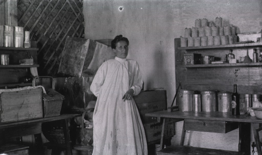 <p>A female worker leans against a box in a kitchen store room in a German Red Cross Hospital.</p>