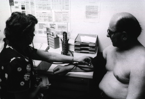 <p>A woman sitting at a desk is checking the blood pressure of a man sitting next to her.</p>
