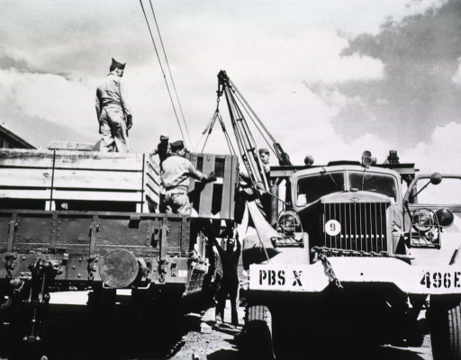 <p>A truck with a crane is parked next to another flat-bed truck.  Men stand on the bed of the truck and guide a crate of materials attached to the crane onto the bed of the truck.</p>