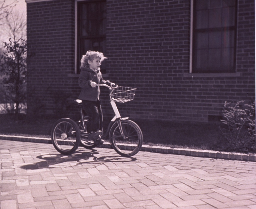 <p>A girl is riding on a large tricycle.</p>