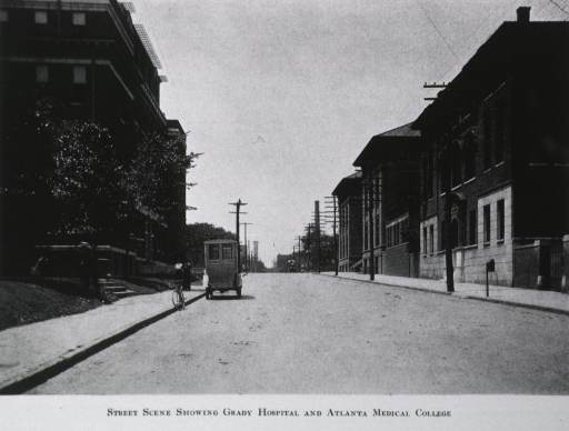 <p>Exterior view: looking south on Butler Street the Atlanta Medical College is on the right and the Grady Hospital is on the left.  A small truck and a bicycle are at the curb in front of the hospital.</p>