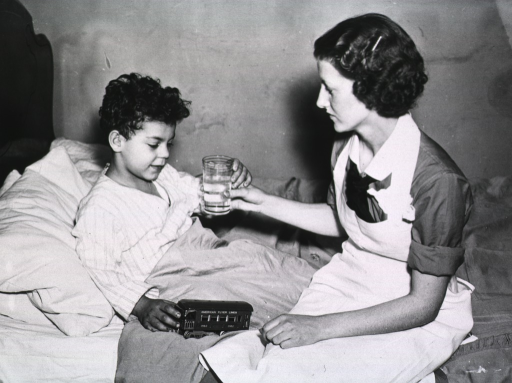 <p>A nurse gives a sick young boy a glass of water while he is in bed.</p>