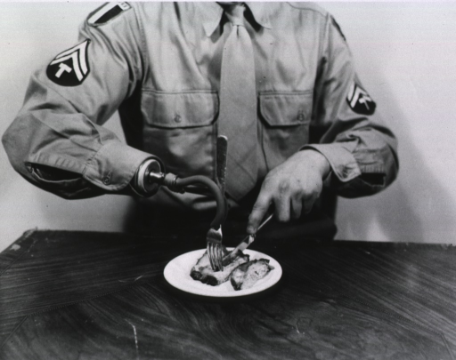 <p>View of a man in military uniform shown from the neck down sitting at a table.  The man holds a fork in his prosthetic right hook and with his left hand cuts a piece of meat on a plate.  The man wears a shirt and tie.  On either arm of the shirt are two military patches, the bottom one on both arms (a double chevron surmounting the letter &quot;T&quot;) representing a Technician 5th Grade.  (The same man appears in another photograph (Prosthesis no. 24 box 1 mil).)</p>
