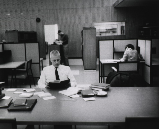 <p>Interior view: A man is sitting at a table.  On the table are books, a pen, and an ashtray.  There is a woman sitting at a study carrel.  In the background a man is standing looking at material that is resting on a shelf.</p>
