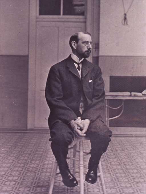 <p>Full length, seated on stool, head turned to right almost in profile; wearing glasses.</p>
