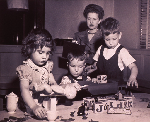 <p>A woman is noting the reactions of three children playing with different toys.</p>