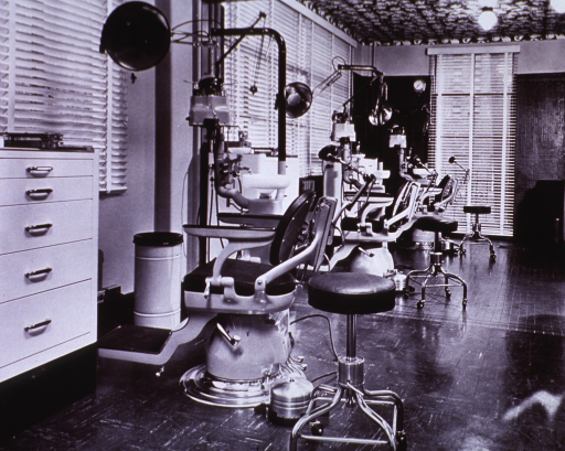 <p>Interior view: three chairs, dental units, and stools face windows with Venetian blinds.</p>
