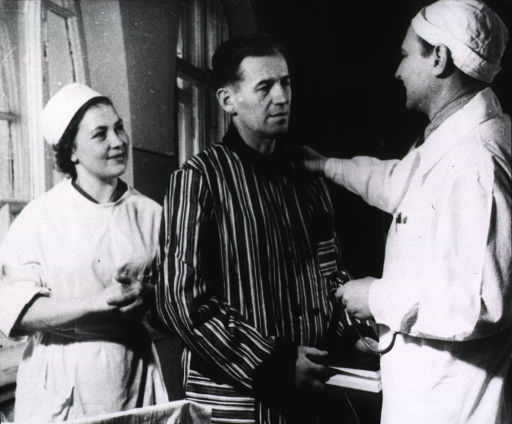 <p>A physician is standing with a patient; a nurse is standing behind them.</p>