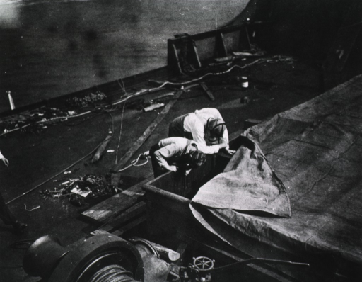 <p>View of two members from a League of Nations team of fumigation experts, wearing gas masks, peering into a ship's hatch.</p>