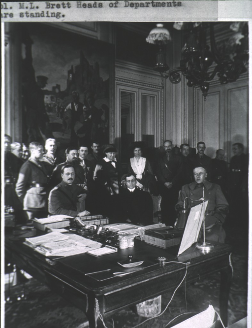 <p>Large group showing Newton Baker and Anna C. Ladd seated by table, others standing in background.</p>
