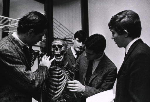 <p>Interior view: four medical students are standing with the skeleton of William Burke, all are shown half-length.</p>