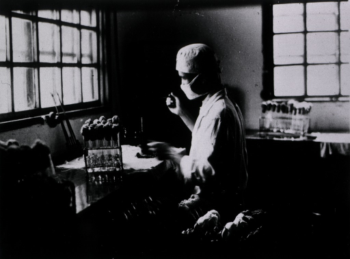 <p>Interior view: test tubes are on a counter at which a man with a mask is sitting.</p>