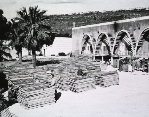 <p>Piles of window frames sit next to a partially built edifice.  Several servicemen are seen walking amidst the piles.</p>