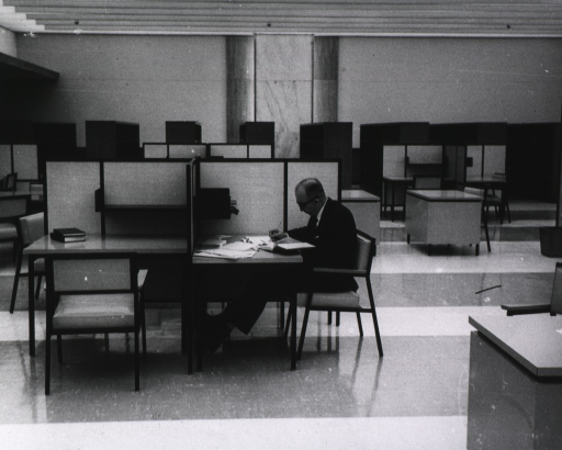 <p>Interior view: A man is sitting at a carrel; books are on an adjacent carrel.  In the background are empty shelves.</p>