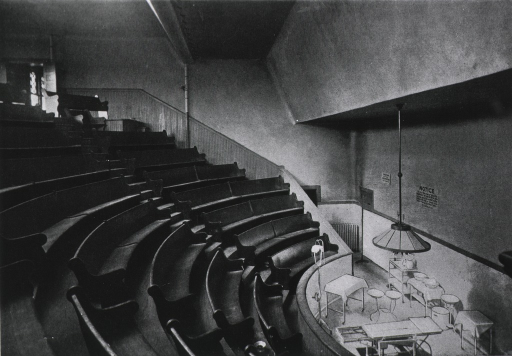 <p>Interior view: surgical amphitheatre with marble wainscoting and a white marble tile floor is in the Main Building; a spittoon is on the floor of the second row.</p>