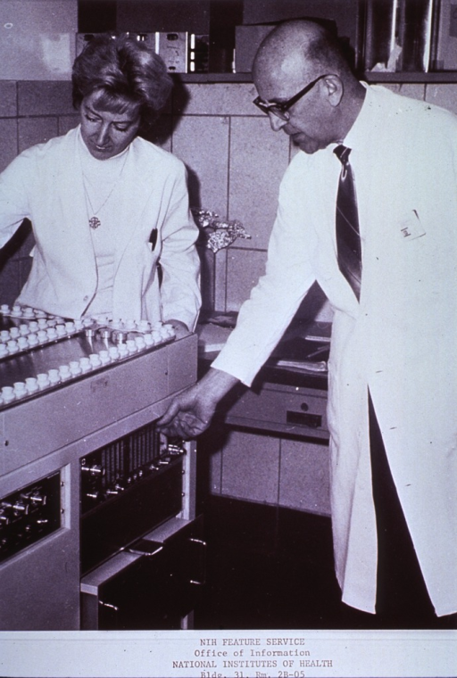 <p>Interior view: a man and a woman adjust the controls on a gamma counter in a laboratory. They are measuring hormone concentrations in the blood and pituitaries using such methods as radio-immuno assays and competitive protein-binding assays.</p>