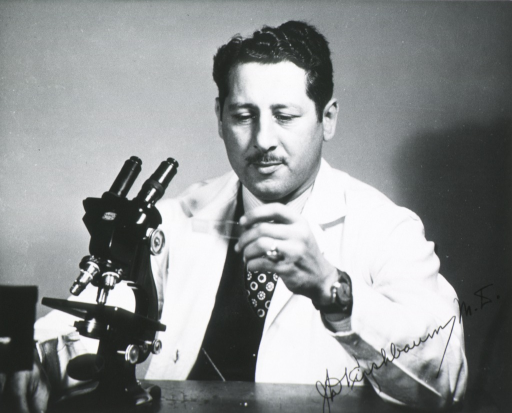 <p>Half-length, seated before microscope, full face; holding slide; wearing white lab coat.</p>