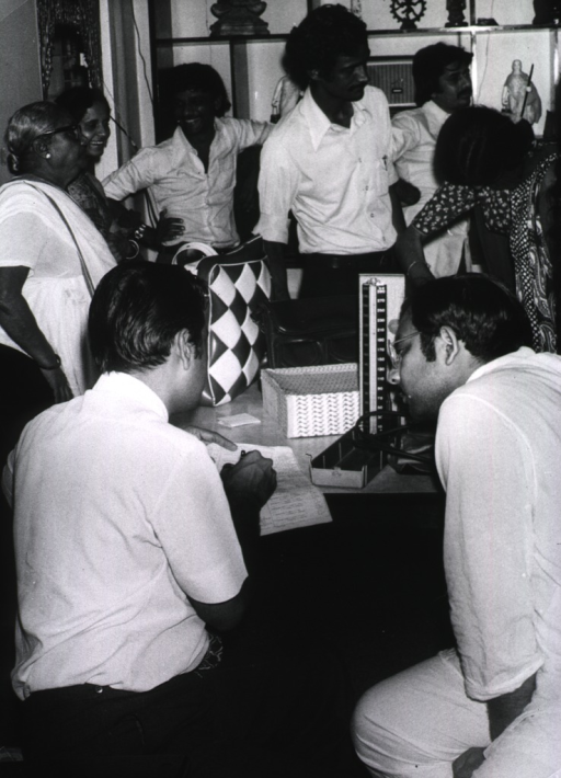 <p>Physicians, in a room of a residence, are taking group blood pressure readings during a gathering in what has the appearence of a party-like atmosphere.</p>